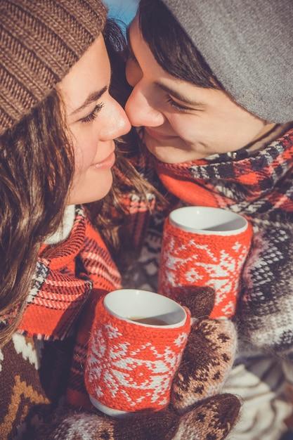 Paar trinkt heißen tee im winterpark Premium Fotos