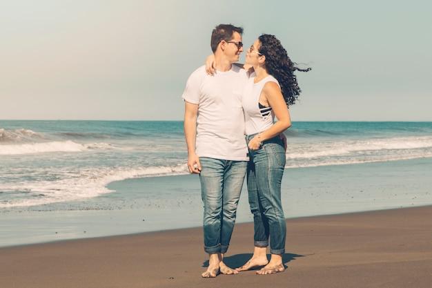 Paar umarmt am sandstrand Kostenlose Fotos