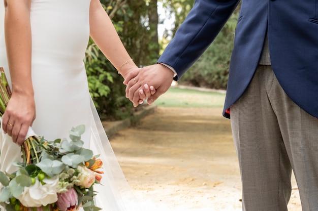 Paar verliebt händchen haltend, sie mit blumenstrauß in einer hand Premium Fotos