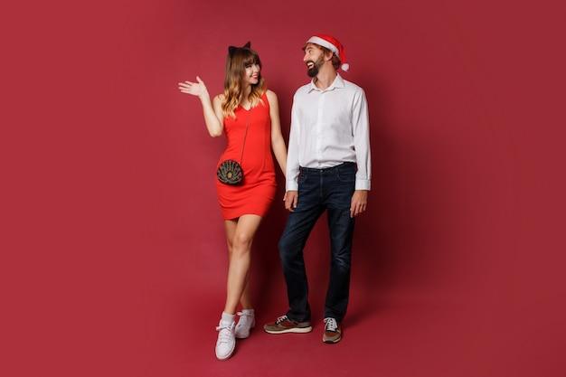 Paar verliebt in neujahrs-maskeradenhüte, die auf rot aufwerfen. partystimmung. Kostenlose Fotos