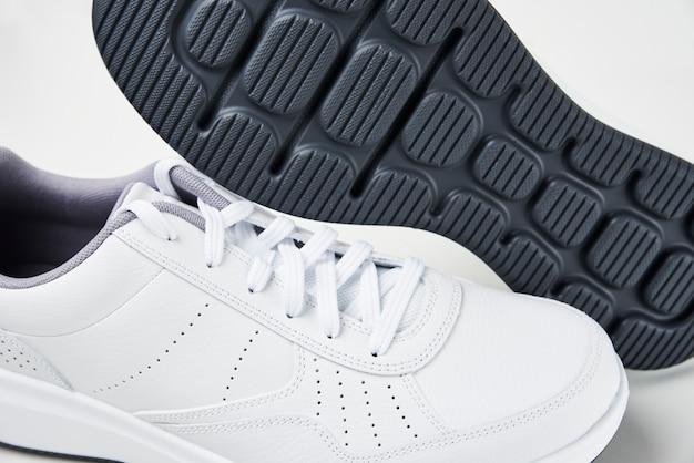 Paar weiße männliche turnschuhe auf weiß. mode stilvolle sportschuhe, nahaufnahme Premium Fotos
