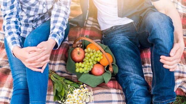 Paare am picknick auf rasen im park Kostenlose Fotos