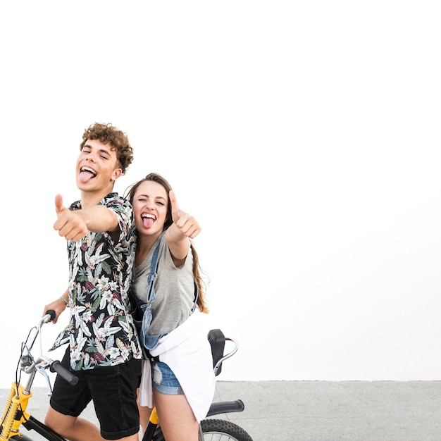 Paare auf der fahrradfahrt, die daumen herauf das neckende zeichen zeigt Kostenlose Fotos