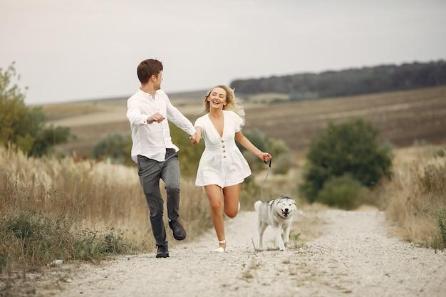 Paare auf einem herbstgebiet, das mit einem hund spielt Kostenlose Fotos