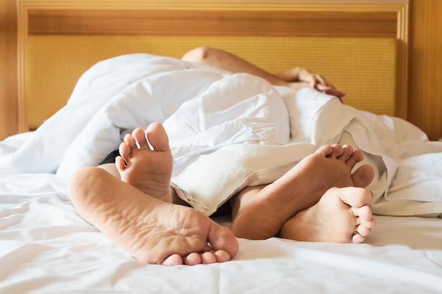Paare auf weißem bett im hotelzimmerfokus an den füßen Kostenlose Fotos