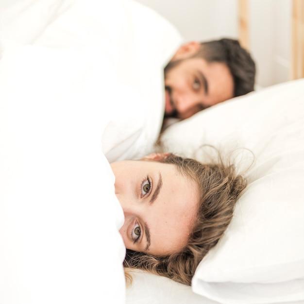 paare bedeckt in der decke die auf bett liegt download der kostenlosen fotos. Black Bedroom Furniture Sets. Home Design Ideas