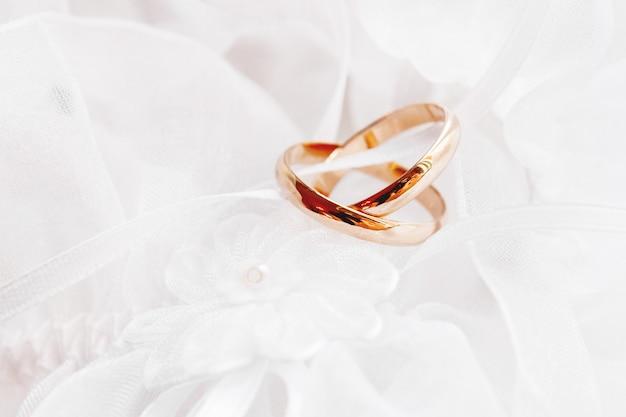 Paare der goldenen eheringe auf silk gewebe der spitzes mit gewebeblume. hochzeit stickerei kleid detail. Premium Fotos