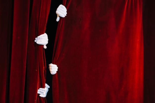Paare der hand des pantomimen, die geschlossenen roten vorhang hält Kostenlose Fotos