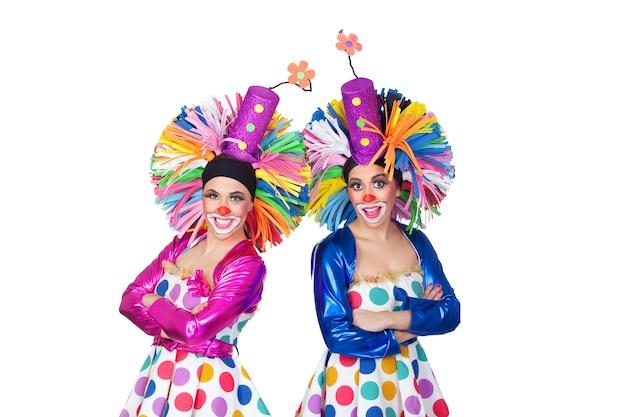 Paare der lustigen clowne mit den großen bunten perücken lokalisiert auf weißem hintergrund Premium Fotos