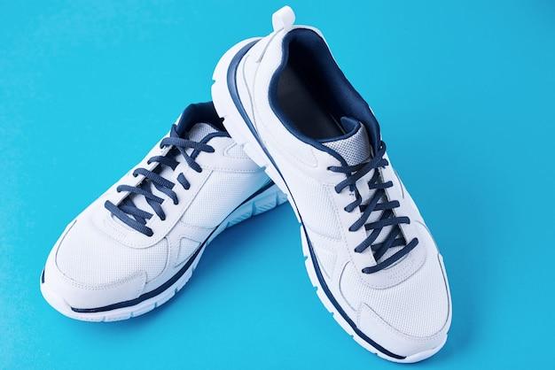 Paare der männlichen weißen turnschuhe auf einem blauen hintergrund. sportschuh hautnah Premium Fotos
