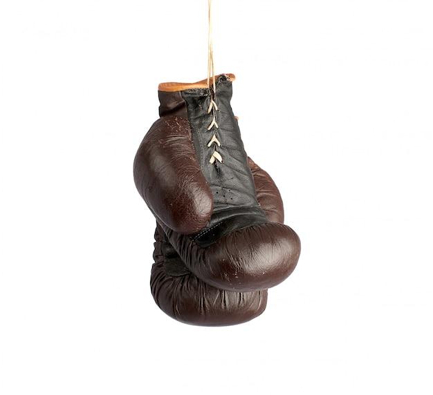 Paare der sehr alten braunen ledernen boxhandschuhe der weinlese, die an einem seil hängen Premium Fotos