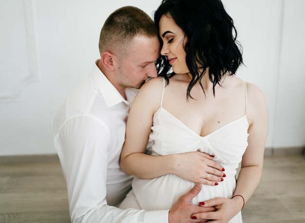 Paare des hübschen ehemanns und der hübschen pragnant frau, die am studio aufwerfen Kostenlose Fotos