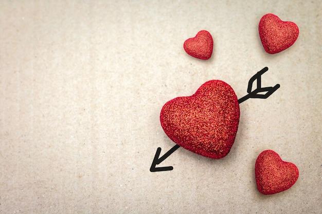 Paare des roten herzens mit amorpfeil auf papphintergrund. Premium Fotos