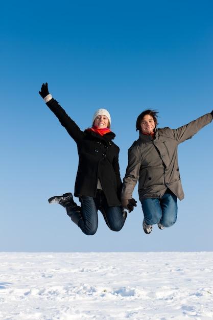 Paare, die an einem wintertag springen Premium Fotos