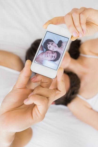 Paare, die auf bett liegen und ein selfie am handy nehmen Premium Fotos