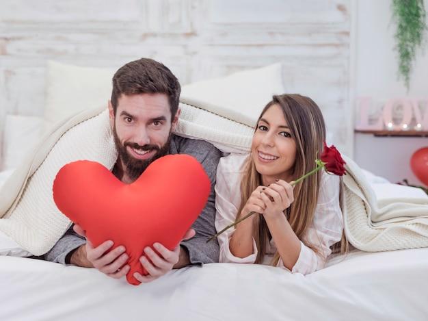 Paare, die auf bett mit weichem rotem herzen liegen Kostenlose Fotos