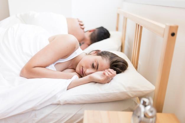 Paare, die auf bett schlafen Kostenlose Fotos