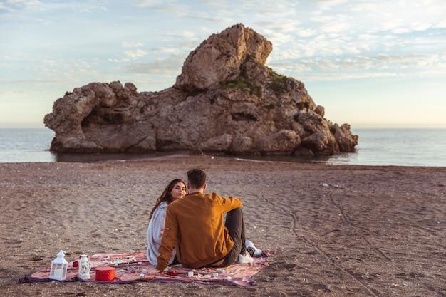 Paare, die auf bettdecke auf seeufer sitzen Kostenlose Fotos