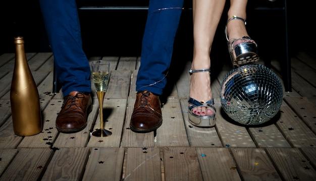Paare, die auf bretterboden mit discokugel und -champagner stehen Kostenlose Fotos