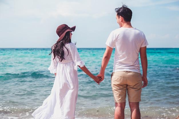 Paare, die auf dem strand mit einem schönen sonnenuntergang im hintergrund küssen. Premium Fotos