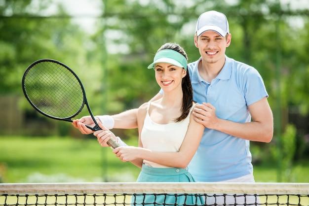 Paare, die auf dem tennisplatz, tennisschläger halten stehen. Premium Fotos