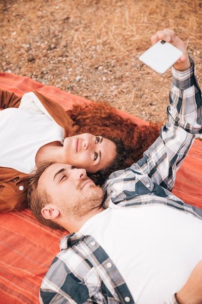 Paare, die auf der decke nimmt ein selfie liegen Kostenlose Fotos