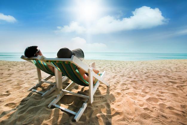 Paare, die auf einem strandstuhl und -regenschirm ein sonnenbad nehmen Premium Fotos