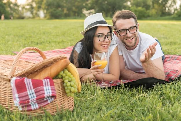 Paare, die auf einer picknickdecke sprechen Kostenlose Fotos