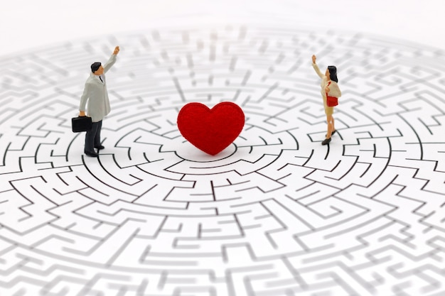 Paare, die auf mitte des labyrinths mit rotem herzen stehen. Premium Fotos