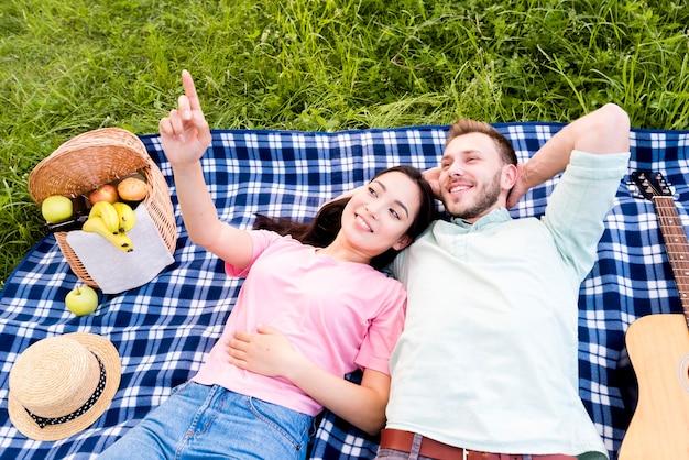 Paare, die auf picknickdecke liegen Kostenlose Fotos