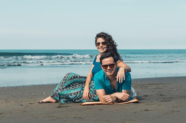 Paare, die auf sandigem strand stillstehen Kostenlose Fotos