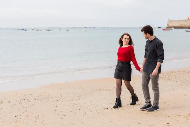 Paare, die auf sandiges seeufer gehen und sprechen Kostenlose Fotos