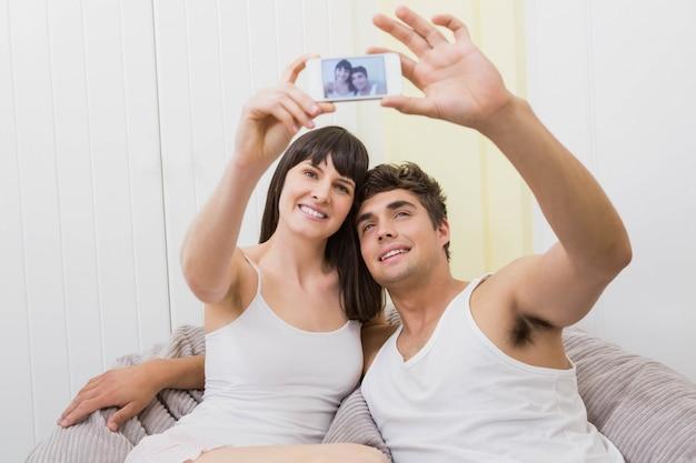 Paare, die auf sofa liegen und ein selfie am handy nehmen Premium Fotos