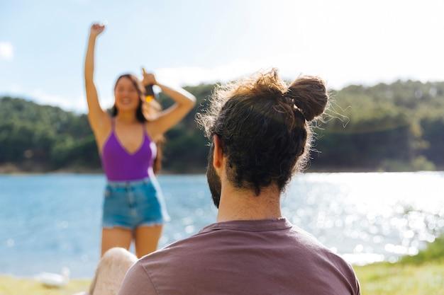 Paare, die auf sonnigem flussufer stillstehen Kostenlose Fotos