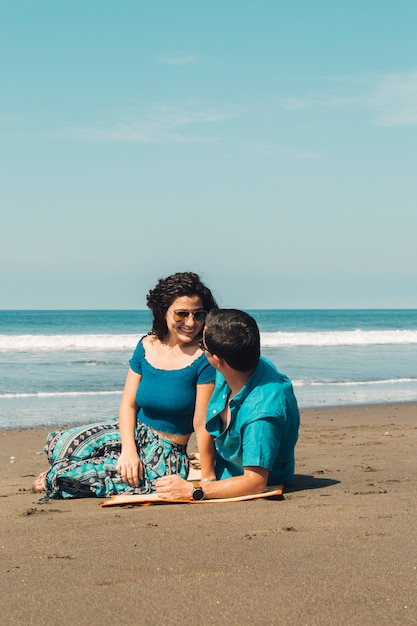 Paare, die auf strand sitzen und einander betrachten Kostenlose Fotos
