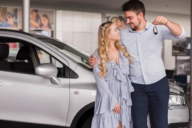Paare, die autoschlüssel halten und einander betrachten Kostenlose Fotos
