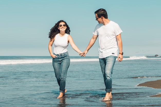 Paare, die barfuß entlang küste in wasser gehen Kostenlose Fotos