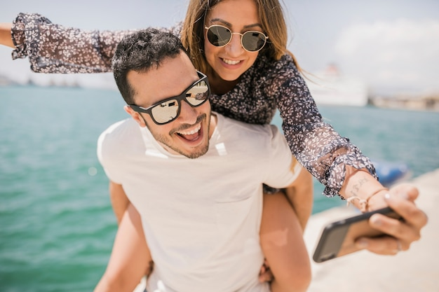 Paare, die das nehmen des selbstporträts am handy genießen Kostenlose Fotos