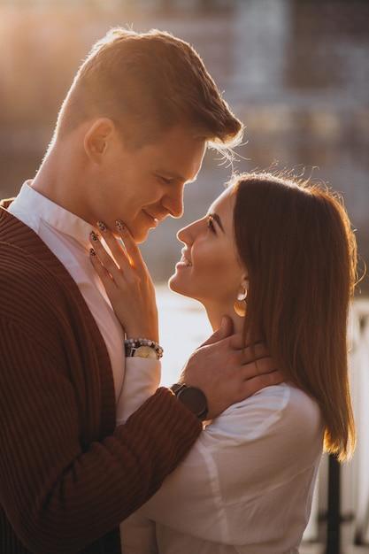 Paare, die draußen durch den fluss umfassen Kostenlose Fotos