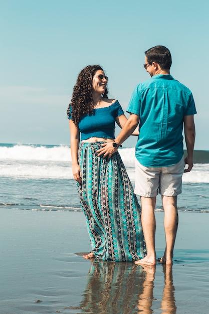 Paare, die durch die taille stehen auf strand umarmen Kostenlose Fotos