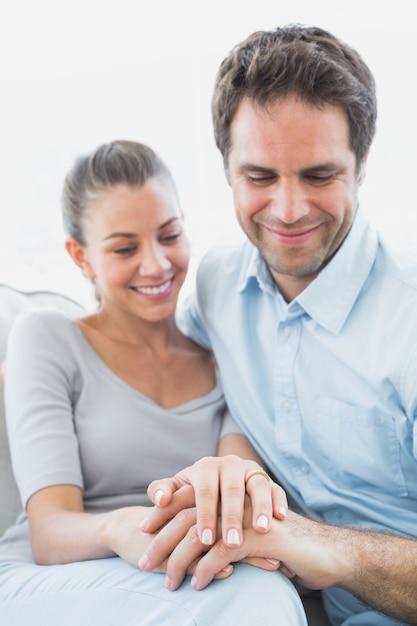 Paare, die ehering auf dem finger der frau auf der couch betrachten Premium Fotos