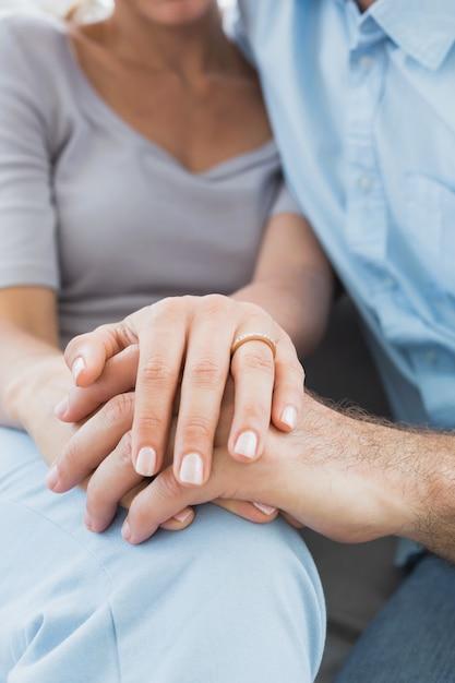 Paare, die ehering auf dem finger der frau auf der couch zeigen Premium Fotos