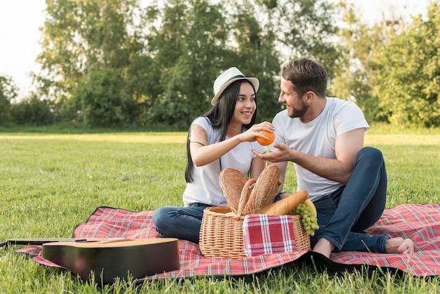 Paare, die eine orange auf einer picknickdecke nehmen Kostenlose Fotos