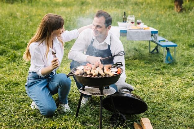 Paare, die einen grill in der natur tun Kostenlose Fotos