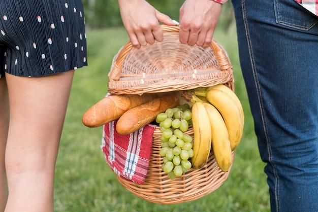 Paare, die einen weg hält einen picknickkorb haben Kostenlose Fotos