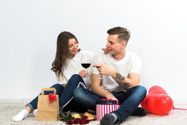 Paare, die gläser wein auf fußboden klopfen Kostenlose Fotos