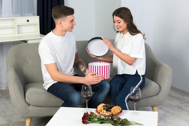 Paare, die große geschenkbox auf couch öffnen Kostenlose Fotos