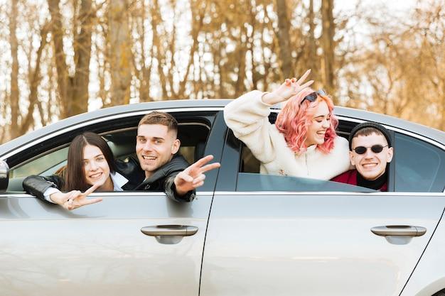 Paare, die im autofenster aufwerfen und friedensgeste zeigen Kostenlose Fotos