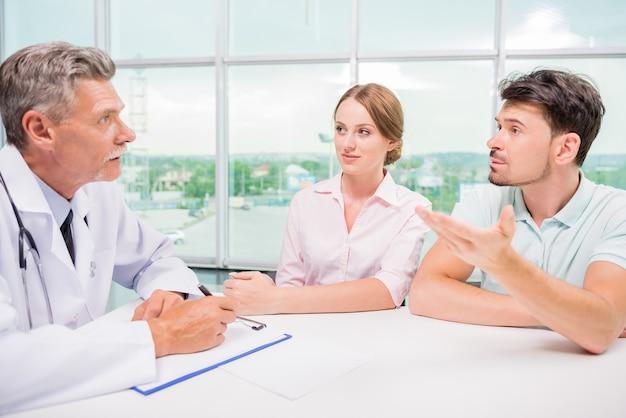 Paare, die im büro sitzen und mit praktiker sprechen. Premium Fotos