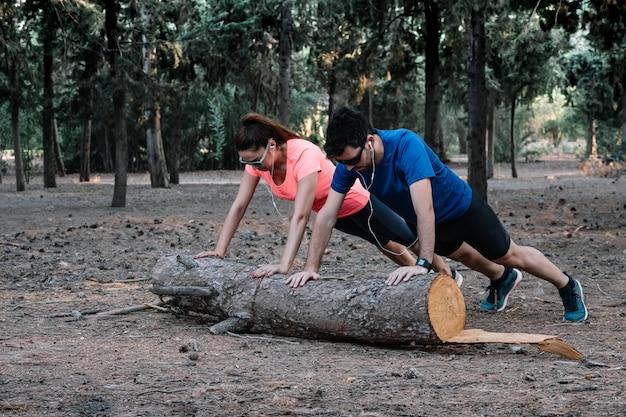 Paare, die liegestütze auf einer anmeldung ein park tun Premium Fotos